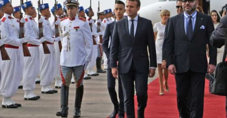 Moroccan King Mohammed VI (R) walks alongside French President Emmanuel Macron as they review the honour guard upon the latter's arrival in Rabat on June 14, 2017.  By ALAIN JOCARD (POOL/AFP)