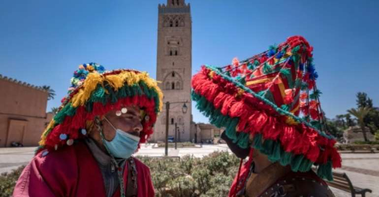 Moroccan water sellers, who have been impacted by the Covid-19 crisis since its start due to the scarcity of tourism, chat in front of the Koutoubia mosque in the city of Marrakesh.  By FADEL SENNA (AFP)