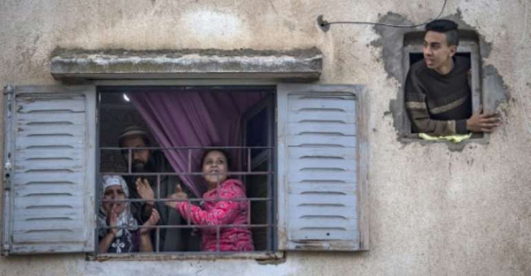 Moroccans confined at home thank the authorities from their windows as security forces and health workers instruct people to return to and remain at home as a measure against the COVID-19 coronavirus pandemic, in Rabat's district of Takadoum.  By FADEL SENNA (AFP)