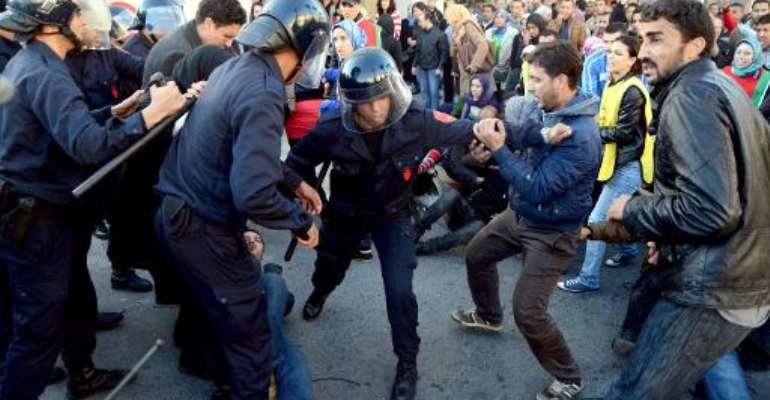 Moroccan police clash with protestors after they tried to climb the barrier of the parliament building in the capital Rabat during a demonstration held by unemployed citizens on November 20, 2013.  By  (AFP)