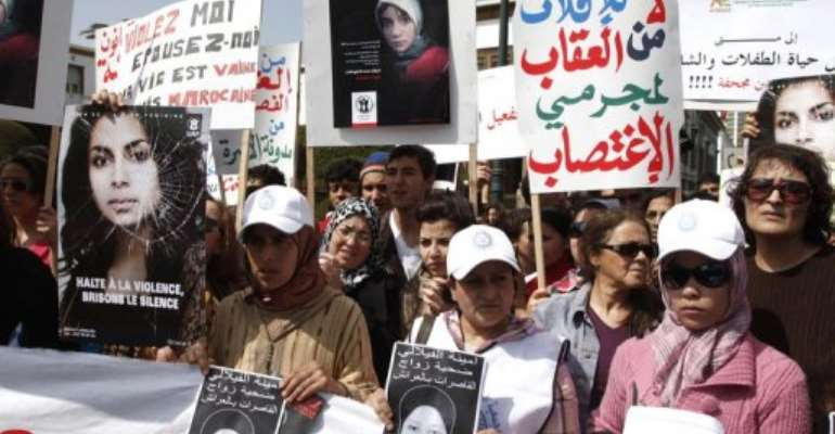 Women hold posters as they demonstrate outside the Moroccan parlament in Rabat, on March 17, 2012.  By  (AFP/File)