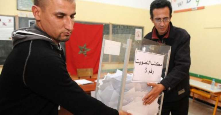 Electoral agents carry the ballot box prior vote counting.  By Abdelhak Senna (AFP)