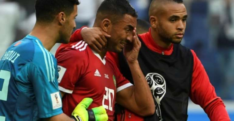 Morocco's Aziz Bouhaddouz is consoled by teammates after he scored an own goal against Iran at the World Cup.  By Paul ELLIS (AFP)