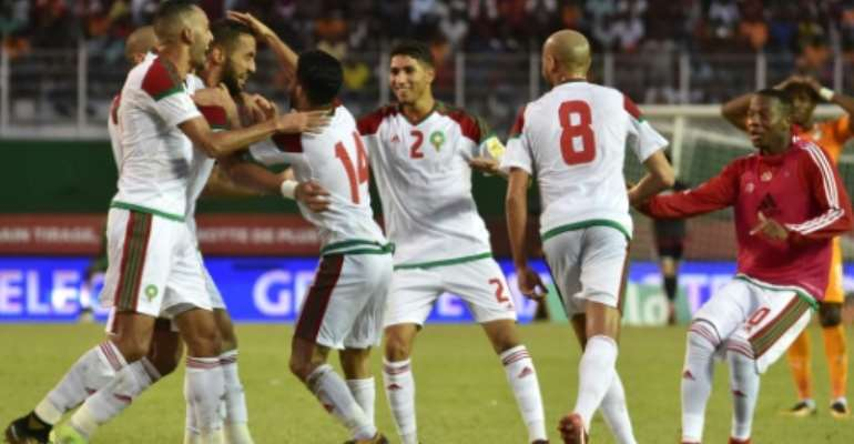 Morocco's team players celebrate a goal against Cote d'Ivoire at the Felix Houphouet-Boigny stadium in Abidjan on November 11, 2017.  By ISSOUF SANOGO (AFP)