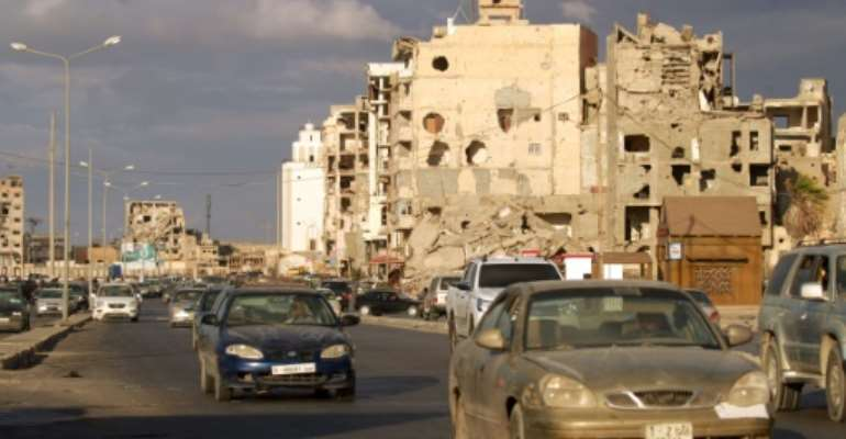 Motorists drive past war-damaged buildings in Libya's main eastern city of Benghazi, where businessmen are desperate for Friday's