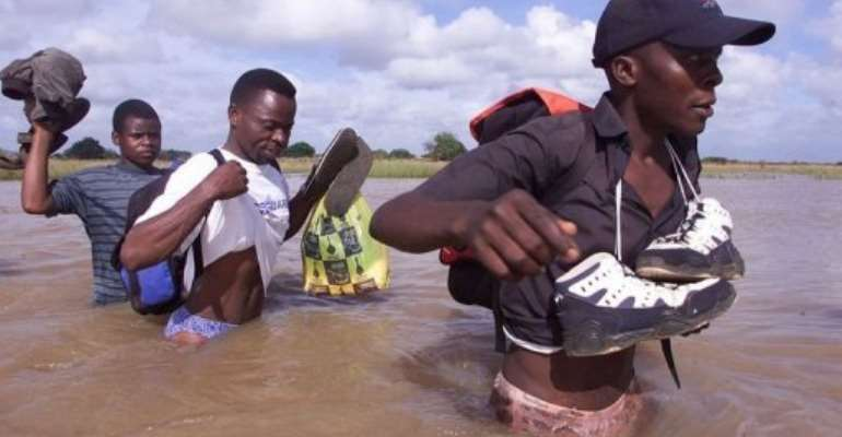 Mozambicans cross a flooded area close to Palmeria on February 25, 2000.  By Yoav Lemmer (AFP/File)