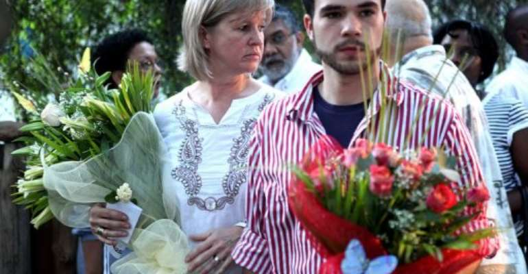 Nina Berg, the widow (right) and son of Carlos Cardoso carry flowers at his monument in Maputo, November 22, 2010.  By Benoit Marquet (AFP/File)