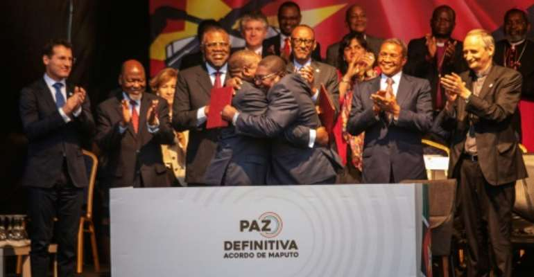 Mozambique's President Filipe Nyusi (C-L) and Renamo (Mozambican National Resistence) leader Ossufo Momade (C-R) embraced after signing the deal.  By STRINGER (AFP)