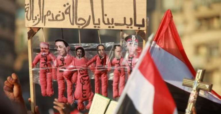 Egyptian protesters hold a banner during a demonstration in Cairo's landmark Tahrir Square.  By Khaled Desouki (AFP)