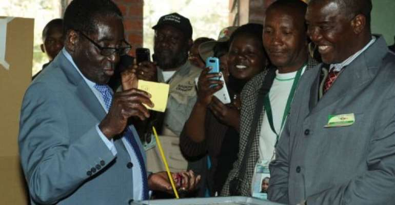 Zimbabwe President Robert Mugabe (L) casts his vote at a polling booth in a school in Harare on July 31, 2013.  By Alexander Joe (AFP)