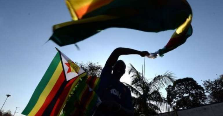 A vendor sells flags on a street in Harare on August 21, 2013, the eve of President Mugabe's inauguration ceremony.  By Alexander Joe (AFP)