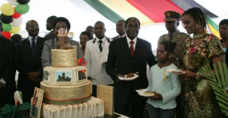 Zimbabwe President Robert Mugabe (4th R) with his birthday cake at celebrations at the State House on February 20, 2013.  By Jekesai Njikizana (AFP)