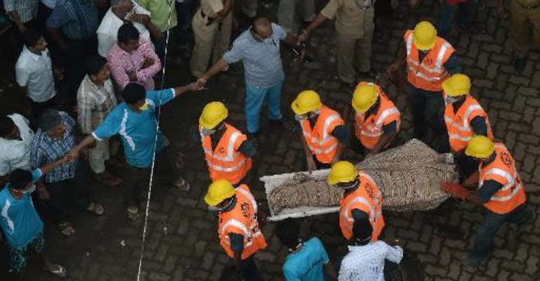 Indian personnel from the National Disaster Relief Force (NDRF) carry a body from the debris of a building collapse site in Mumbai on September 28, 2013.  By Punit Paranjpe (AFP)