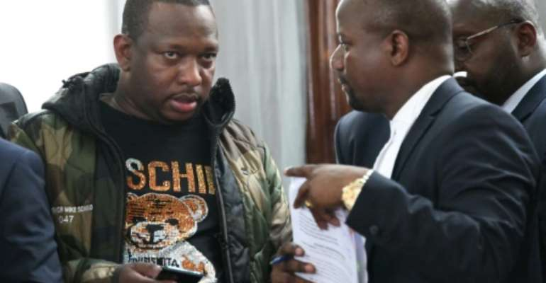 Nairobi Governor Mike Sonko (L), seen here in court in Nairobi on Monday, is known for his style mimicking an American rapper.  By SIMON MAINA (AFP)