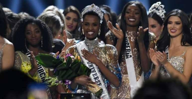 Newly crowned Miss Universe 2019 South Africa's Zozibini Tunzi (C) poses on stage with contestants after the 2019 Miss Universe pageant at the Tyler Perry Studios in Atlanta, Georgia.  By VALERIE MACON (AFP)