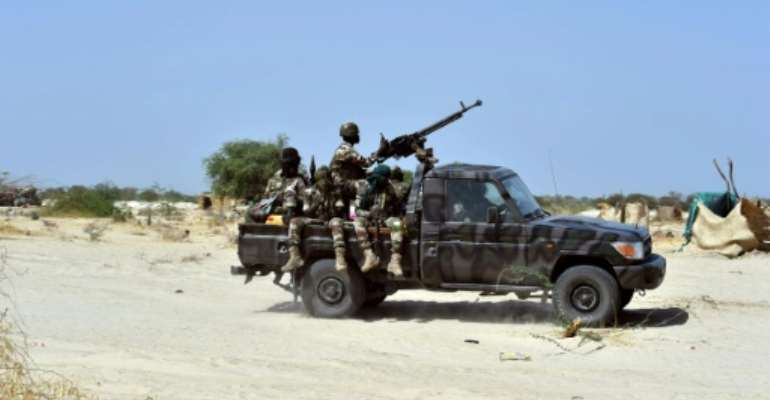 Niger soldiers ride in a military vehicle on May 25, 2015 in Malam Fatori.  By Issouf Sanogo (AFP/File)
