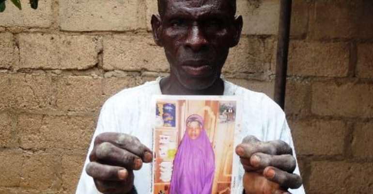 Sani Garba holds a picture of his daughter-in-law Wasila Tasi'u on August 10, 2014 inside her abandoned matrimonial home in the village of Unguwar Yansoro, outside Kano.  By Aminu Abubakar (AFP)