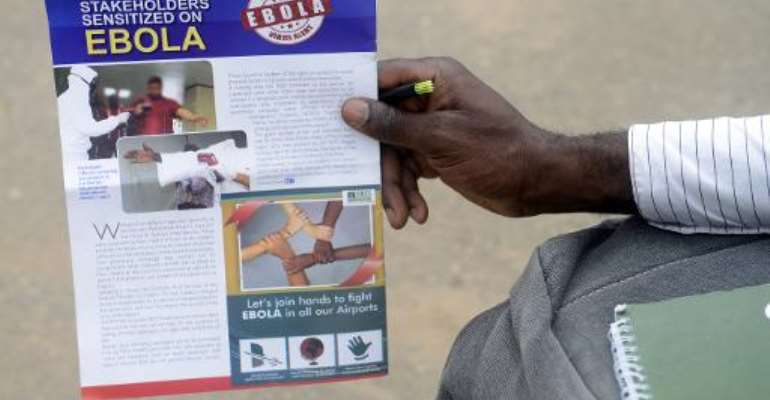 A worker holds a flyer on the Ebola virus at the Murtala Muhammed International Airport in Lagos, Nigeria, on August 11, 2014.  By Pius Utomi Ekpei (AFP/File)