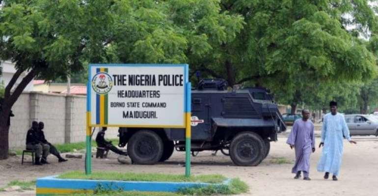 People walk past police armoured tank stationed in Maiduguri.  By Pius Utomi Ekpei (AFP/File)