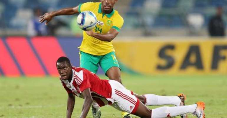 Thulani Hlatshwayo of South Africa challenges Assan Ceesay of Gambia (on the ground) during their Group M, 2017 Africa Cup of Nations qualifying football match on June 13, 2015 in Durban.  By Anesh Debiky (AFP)