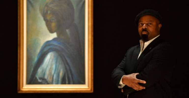Nigerian author Ben Okri poses last year with Ben Enwonwu's 'Tutu' known as the 'African Mona Lisa'.  By BEN STANSALL (AFP)