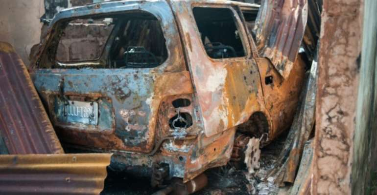 A burnt vehicle is pictured in Nimbo, southeastern Nigeria, where nomadic Fulani herdsman attacked villagers and burnt down buildings and vehicles on May 5, 2016.  By Stefan Heunis (AFP/File)
