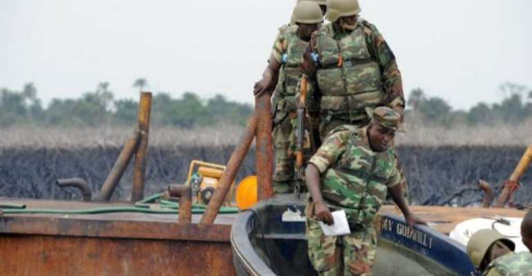 The Joint Take Force inspects a barge seized from oil thieves at Bodo waterways, Ogoniland in Rivers State in 2011.  By Pius Utomi Ekpei (AFP/File)