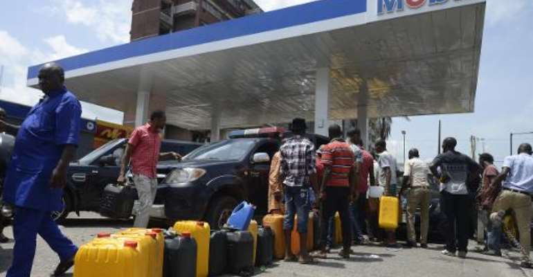 People queue with jerrycans to buy fuel at a Mobil filling station in Lagos on May 21, 2015.  By Pius Utomi Ekpei (AFP)