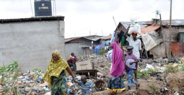A mother and her child walk past shanty homes at Badia East slums in Lagos on August 12, 2013.  By Pius Utomi Ekpei (AFP/File)