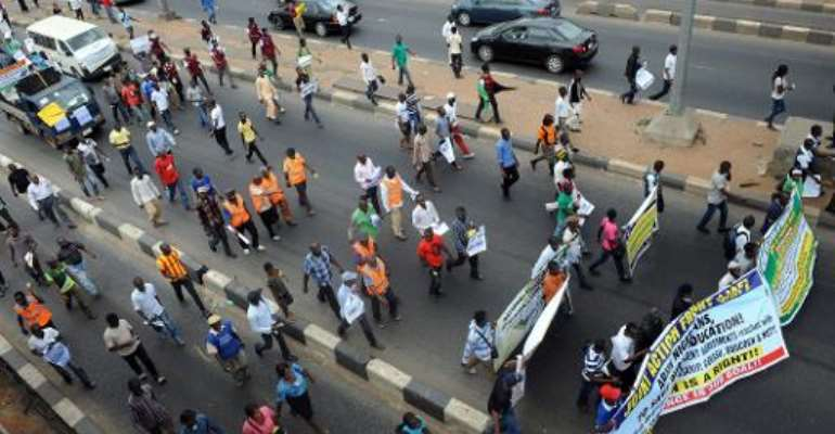 Students and workers carry placards as they march to protest against the suspension of academic activities following a nationwide strike by lecturers in state-owned universities, on August 13, 2013 in Lagos.  By Pius Utomi Ekpei (AFP/File)