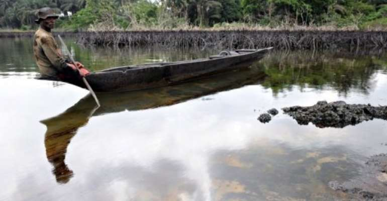 A fisherman looks at spilled crude oil floating in the waters of the Niger Delta swamps of Bodo, in 2010.  By Pius Utomi Ekpei (AFP/File)