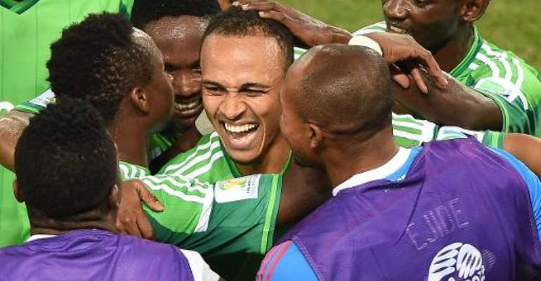 Nigeria forward Peter Odemwingie (C) celebrates with teammates after scoring a goal in their World Cup Group F match against Bosnia-Hercegovina at the Pantanal Arena in Cuiaba on June 21, 2014.  By Luis Acosta (AFP)