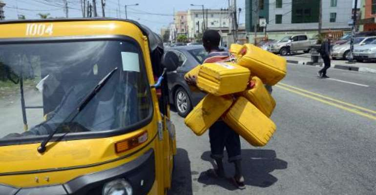 A man carries jerrycans to search for fuel in Lagos, on May 21, 2015.  By Pius Utomi Ekpei (AFP/File)