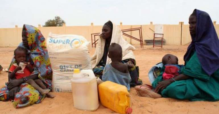 Women watch food being distributed by the UN World Food Programme near Timbuktu in December 2012.  By Omar Barry (Islamic Relief/AFP/File)
