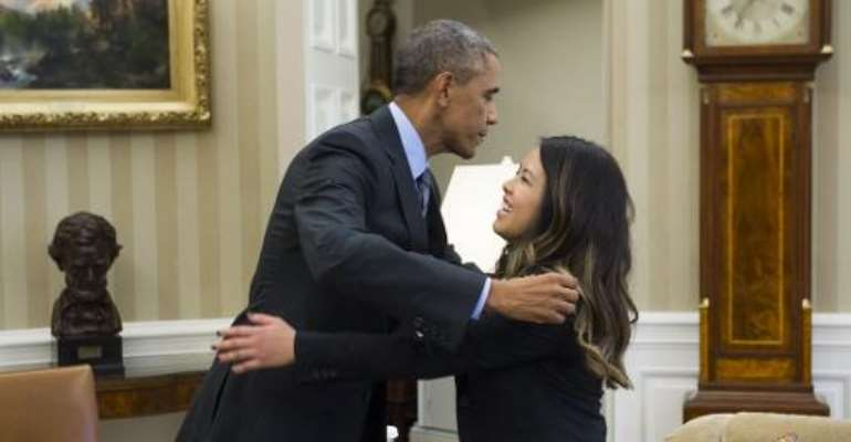 US President Barack Obama hugs nurse Nina Pham, who was declared free of the Ebola virus after contracting the disease while caring for a Liberian patient in Texas, during a meeting in the Oval Office on October 24, 2014.  By Saul Loeb (AFP)