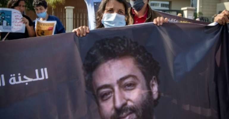 Omar Radi's mother holds a banner picture of her son at a protest in Casablanca in this file picture from September 22, 2020.  By FADEL SENNA (AFP/File)