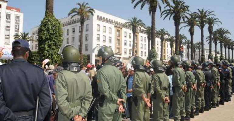 Police and soldiers stand by during a demonstration in front of parliament in Rabat on April 8, 2011.  By Abdelhak Senna (AFP)