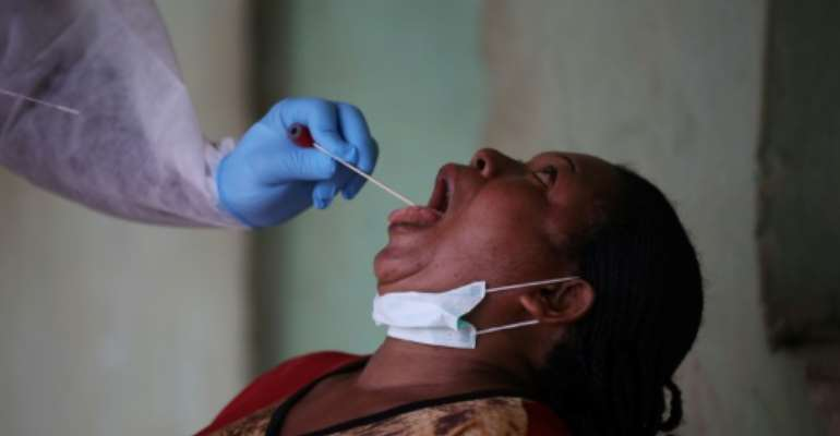 Open wide: A health worker takes a swab during a coronavirus test campaign in the Nigerian capital Abuja.  By Kola Sulaimon (AFP)