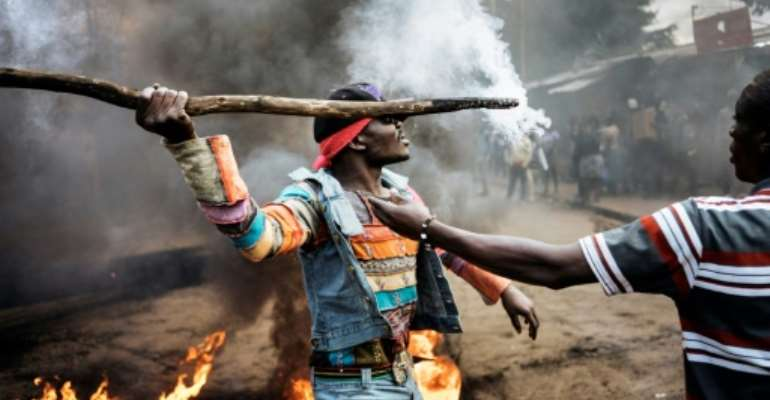 Opposition supporters demonstrate at a burning barricade in Kibera slum in Nairobi on the eve of Kenya's second election in two months.  By MARCO LONGARI (AFP)