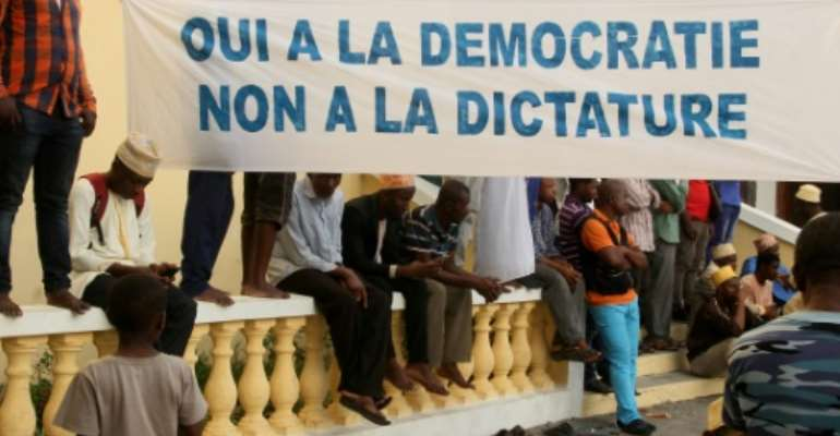 Opposition supporters hold a banner saying 'Yes to democracy, no to dictatorship'.  By Youssouf IBRAHIM (AFP)