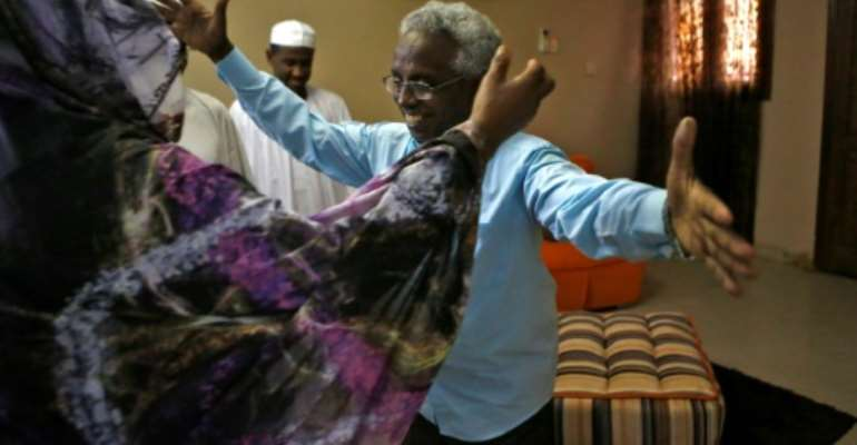 Osman Mirghani, who was released Friday, is greeted by his sister in the Sudanese city of Omdurman.  By ASHRAF SHAZLY (AFP)