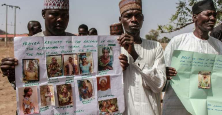 Parents and relatives hold portraits of their girls during a commemoration five years after they were abducted by Boko Haram Jihadists who stormed the Chibok girls' boarding school.  By Audu Ali MARTE (AFP/File)