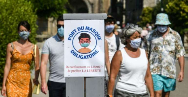 Paris has joined a growing number of French cities requiring people to wear masks in crowded outdoor areas, like the western town of Locronan where the sign instructing passersby to put on masks asks whether they prefer a lockdown or liberty.  By Fred TANNEAU (AFP)