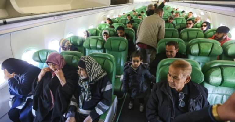Passengers board and sit inside an aircraft at Mitiga airport, east of the Libyan capital Tripoli.  By Mahmud TURKIA (AFP)
