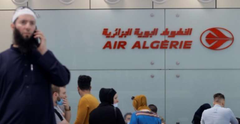 Passengers wait to check in at an Air Algeria counter for a flight to Paris at Algiers' Houari Boumediene Airport.  By - (AFP)