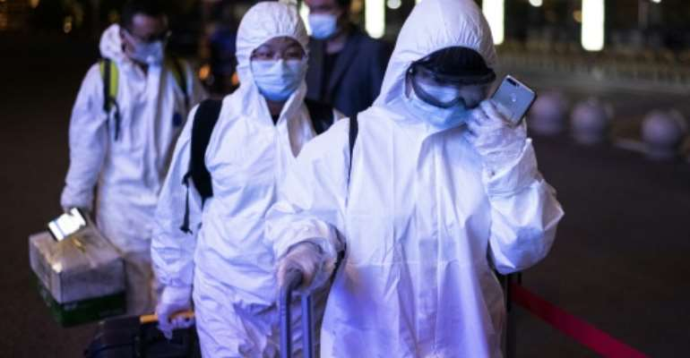 Passengers wear hazmat suits at a Wuhan railway station after a long lockdown was lifted.  By NOEL CELIS (AFP)
