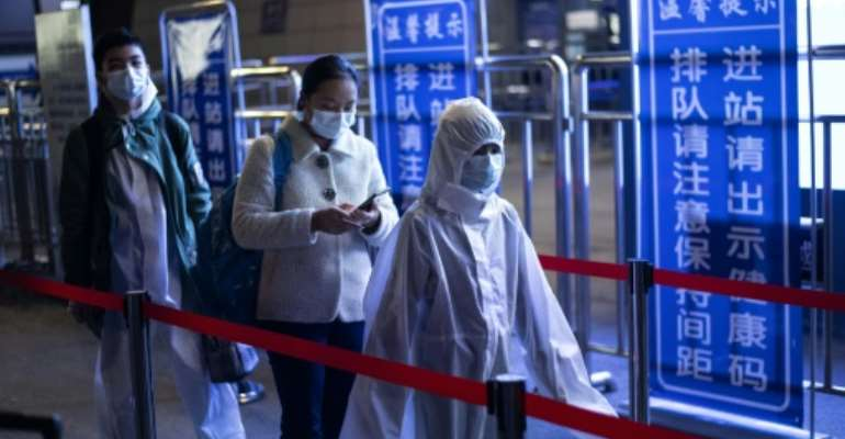 Passengers wear protective clothing as they arrive at the railway station in Wuhan after the authorities lifted a travel ban.  By NOEL CELIS (AFP)