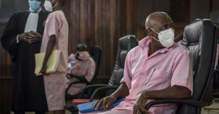 Paul Rusesabagina is seen in February sitting with some of his coaccused at the Supreme Court in Kigali.  By Simon Wohlfahrt (AFP/File)