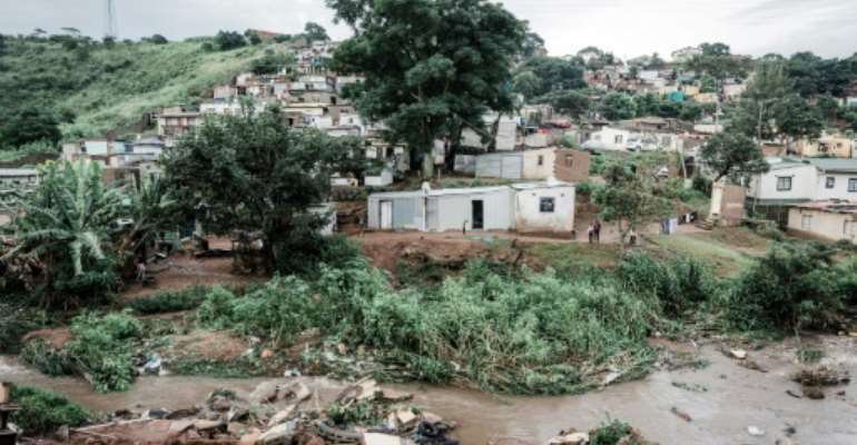 People abandon their homes at an informal settlement of BottleBrush, south of Durban, after torrential rains and flash floods destroyed their homes.  By RAJESH JANTILAL (AFP)