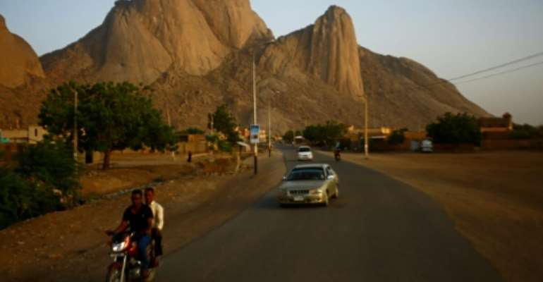 People drive on a road in Sudan's eastern border town of Kassala in front of the Taka Mountains on May 3, 2017.  By ASHRAF SHAZLY (AFP/File)